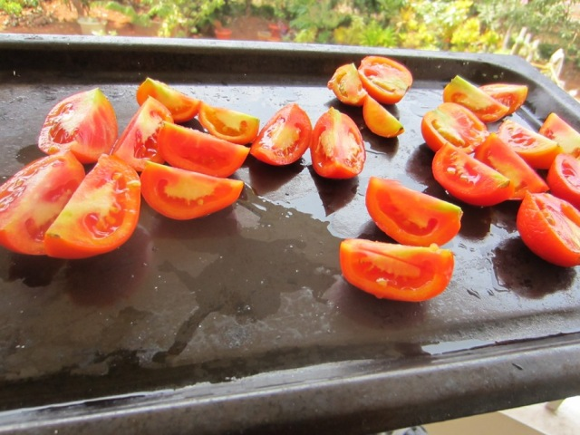 Slit tomatoes, place on baking tray