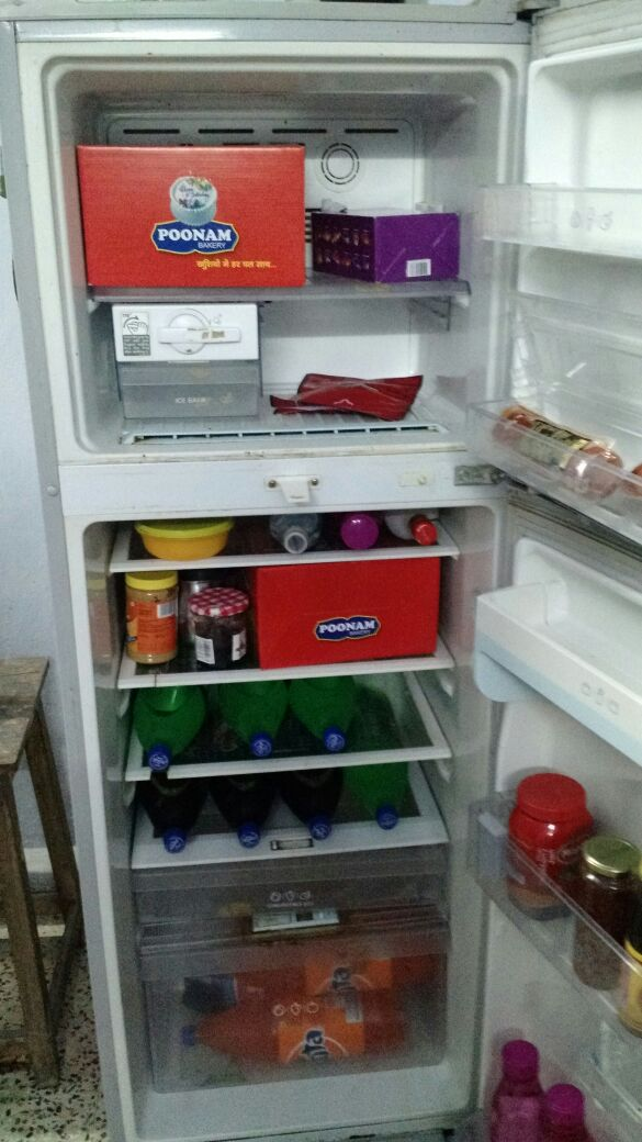 Fridge stocked with cake and drink
